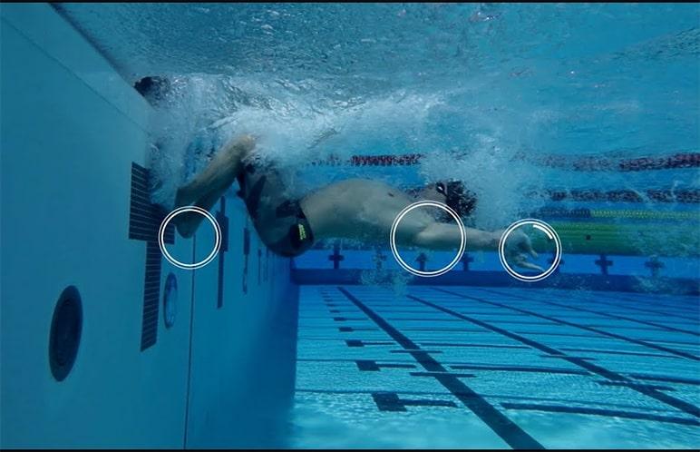 Atleta con corpo allineato in fase di spinta dal muro