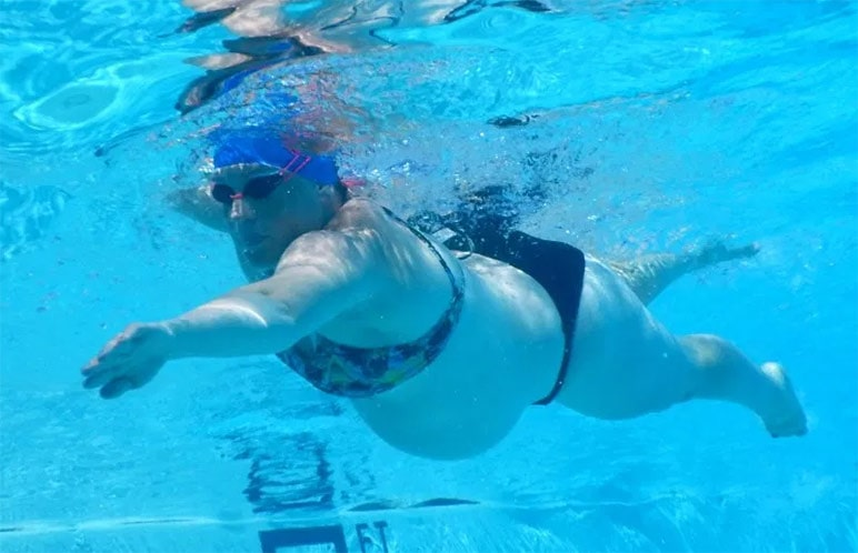 Una nuotatrice master in dolce attesa mentre nuota