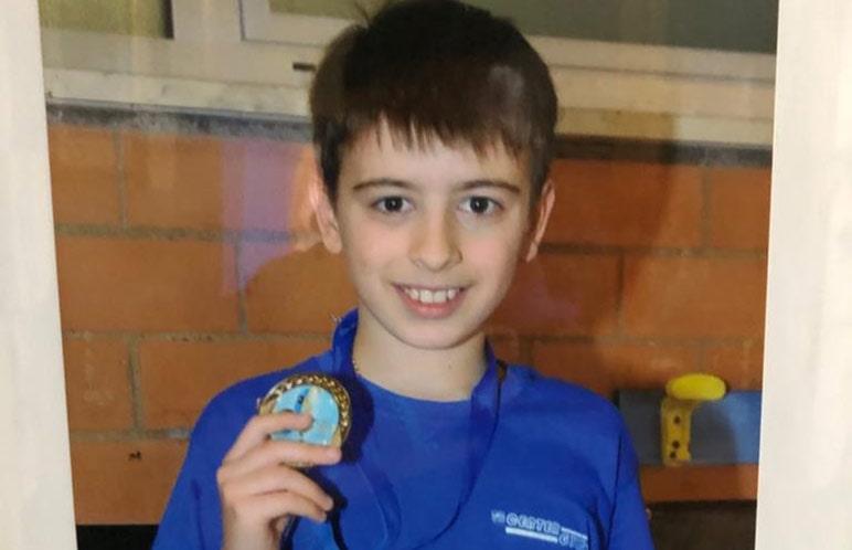 Un bambino del nuoto propaganda felice con la sua medaglia